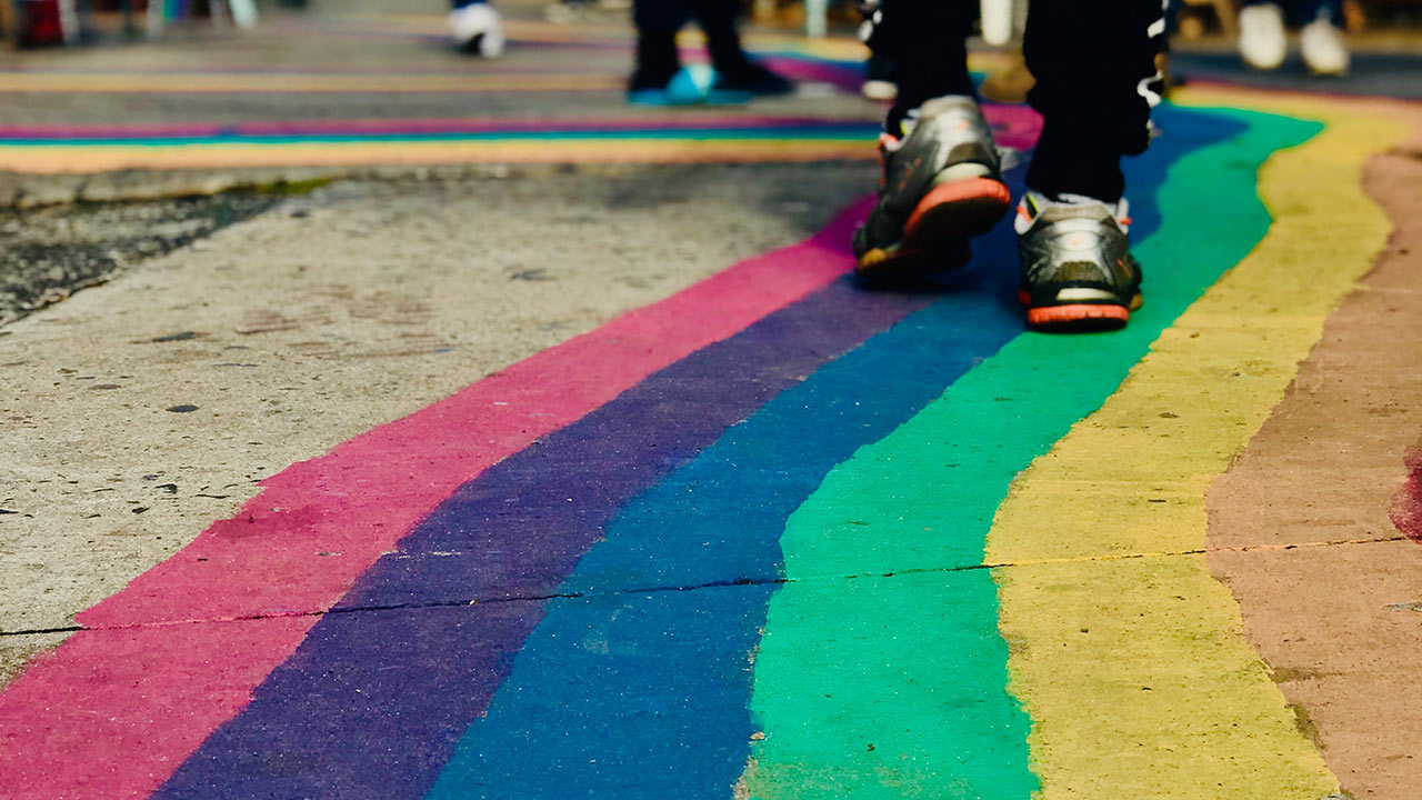 Close-up on the legs of a person wearing sport shoes and walking on a road where a rainbow has been painted on. Photo by Bella The Brave on Unsplash