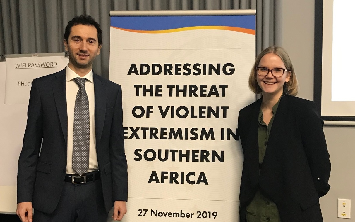 Two EU Analysts in front of event banner