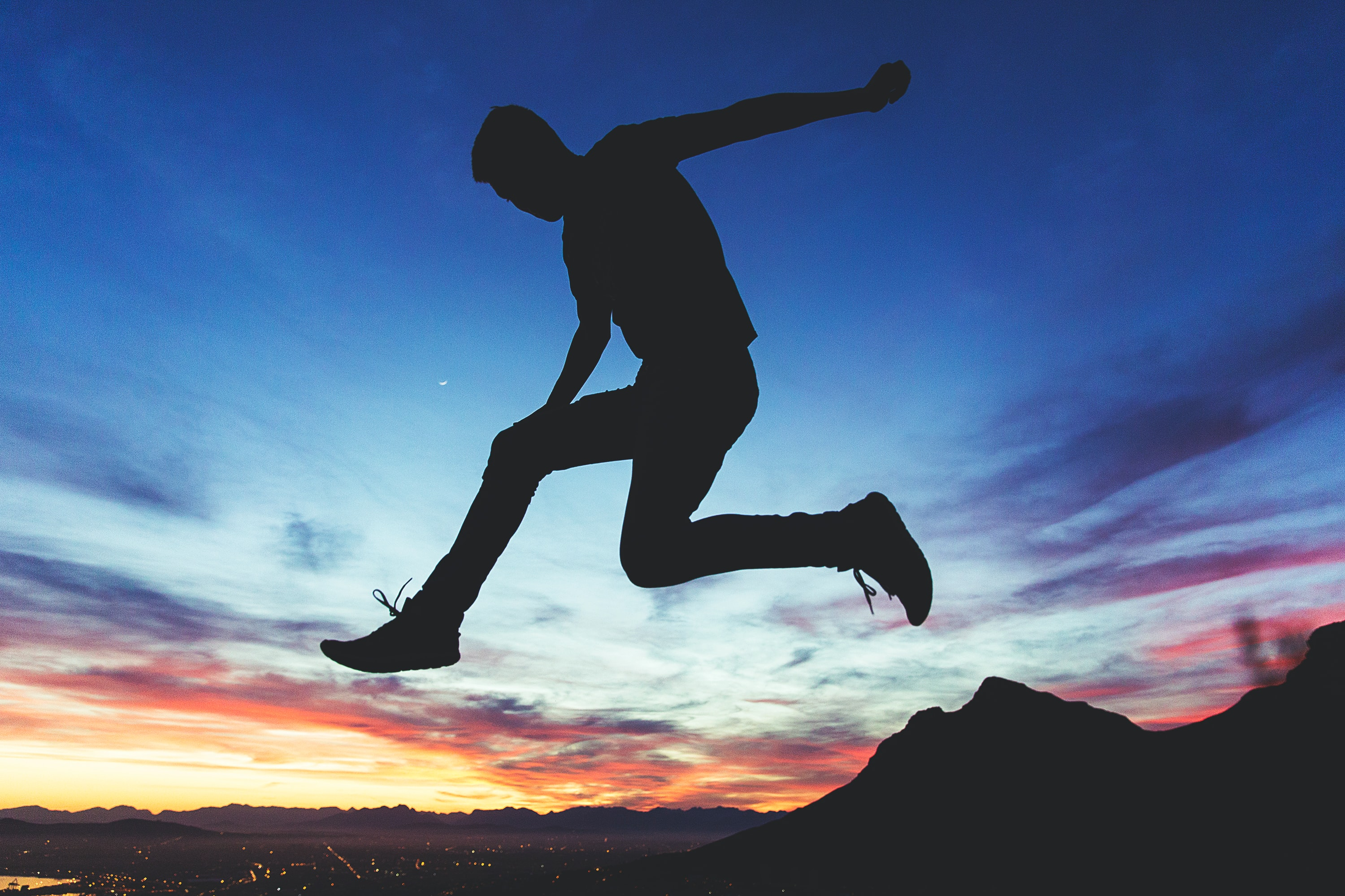 Silhouette of a man jumping with maintains in background