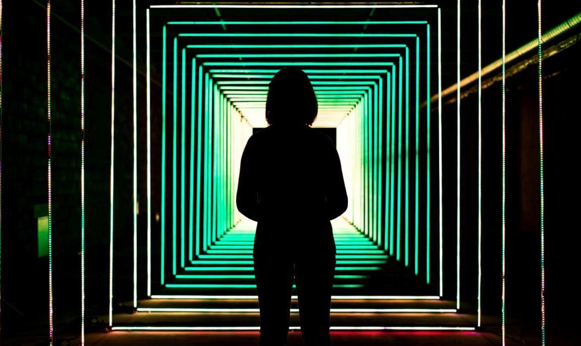 Shadow of a woman standing under fluorecent light - Photo by Bit Cloud on Unsplash