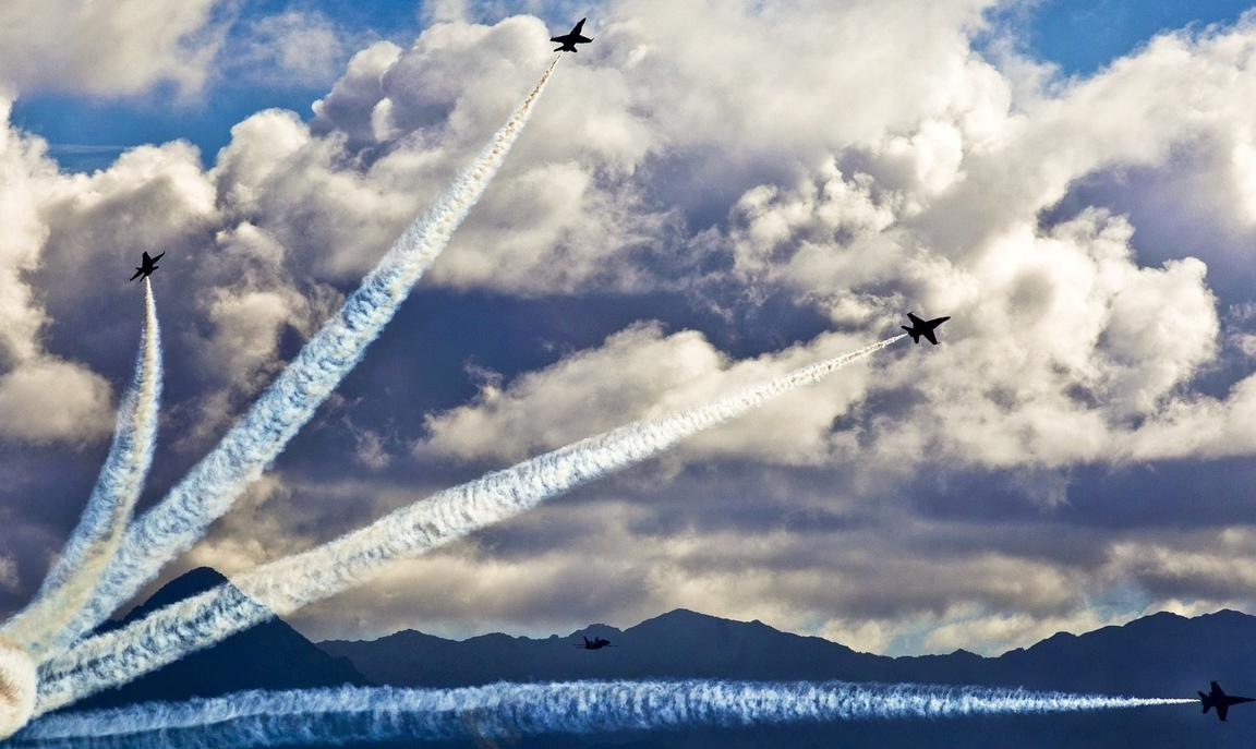 Figher planes in sky leaving trails