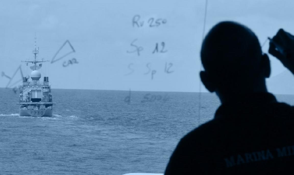 Man drawing on whiteboard with ship in background